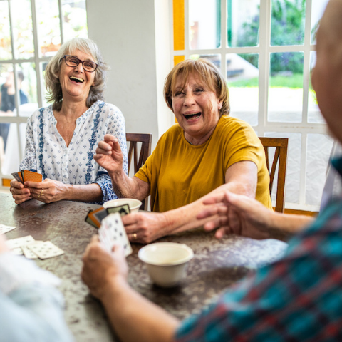 group of seniors smiles while playing card game